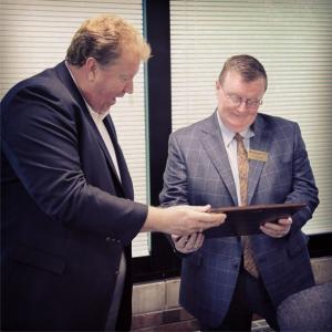 Bob Lane, Executive Director of the NAHA, presents Chancellor Ray Wallace  with a national merit award.