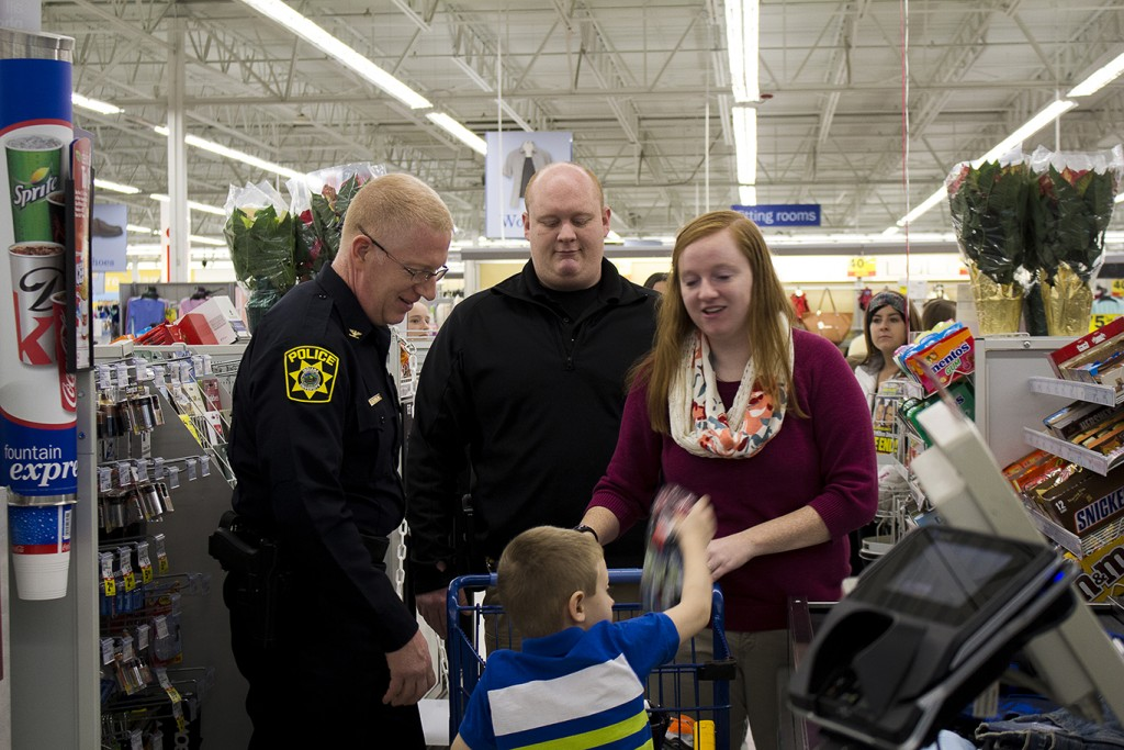 IU Southeast Chief of Police Charlie Edelen (left) shops with a family during Shop With a Cop at Meijer.