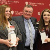 Chancellor Ray Wallace presents award to Ashley Green and Britin Abbot, nursing students.