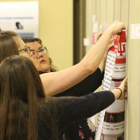 Students pinning posters to the wall.