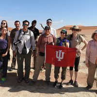 Field Biology travel group hoist IUS banner in Namib Desert.