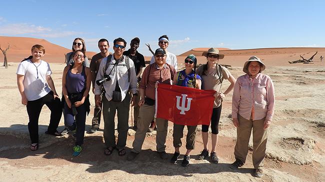 Field Biology travel group hoist IUS banner in Namib Desert.