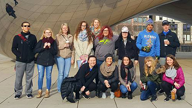 Students of Jennifer Ortiz pose in front of a sculpture on Chicago during a field trip.
