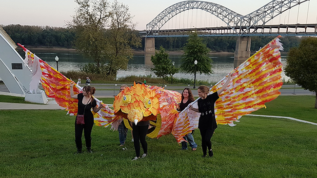 Fine arts students fly phoenix along river.