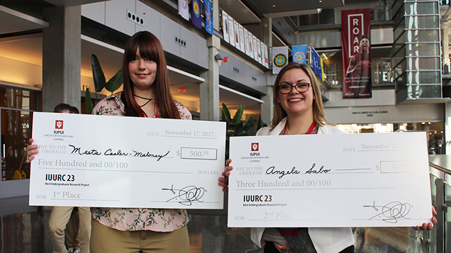 Meeta Cesler-Maloney and Angela Sabo pose with prizes -- two large cheques worth $500 and $300.