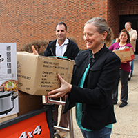 Kelly Ryan, dean of the School of Social Sciences, helps load up donations for Kentucky Refugee Ministries.