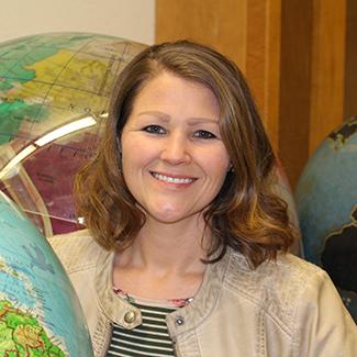 Jennifer Lathem in a classroom with globes
