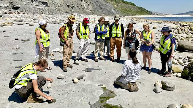 "At Lyme Regis, Chris Andrew (seated), a learning officer for the Lyme Regis Museum, demonstrates to the IU Southeast students how ""worm holes"" are preserved in rocks."