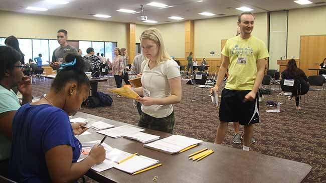 Senior nursing students Emily Hentz and Micah Napper (r) check in for work while Chris Kenny (l) looks on, during the poverty simulation.