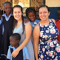 IU Southeast students Emily Mitchell (l) and Ranata Kelly with schoolschildren in the village of Jinja, Uganda.