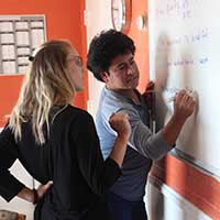 Kelli Kaiser (l) helps equine worker Oscar Navarro build competence in English at the Backside Learning Center inside Churchill Downs.