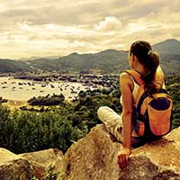 Student admiring panoramic view from mountaintop