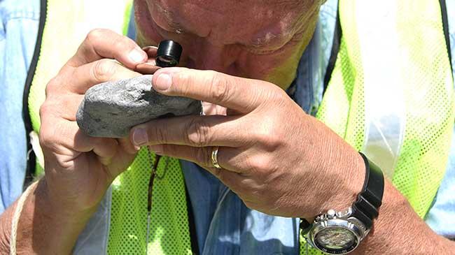 Dr. Glenn Mason inspects a rock with a microscope.