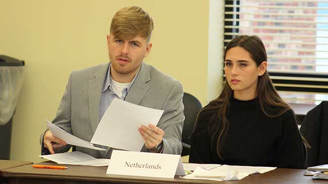 Chandler Morris and Melissa Scianimanico, representing the Netherlands, follow a debate at the Model UN.