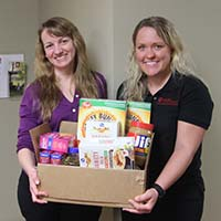 Karen Richie, IU Southeast social worker, receives donated foot items from Alexis Schindler of the IU Southeast SHRM student chapter.
