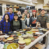 Students pose with donated bowls, together with Keith Kaiser of WDRB and Jason Bige Burnett of the Southern Crossing Pottery Festival.