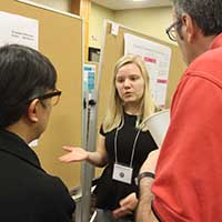 Elizabeth Gillenwater explains her poster on gender inequality in film to two judges.