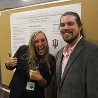 Students Tewsdaay Babicka and Zachary Blasko smiling in front of their poster.