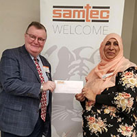 Chancellor Dr. Ray Wallace and Dr. Sumreen Asim with cheque at Samtec.