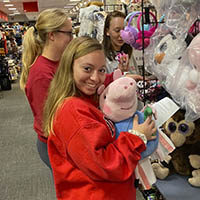 Lindsey Keen, a junior softball player at IU Southeast, picks out a pink pig for the Angel Tree initiative.