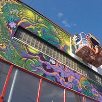 Installing dragon mural on side of building